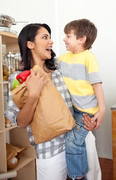 Симпатичный маленький мальчик, распаковывающий продуктовый портфель с матерью Premium Фотографии