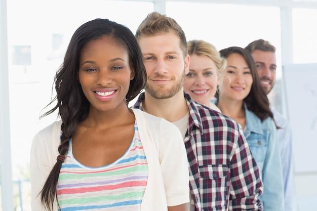 Разнообразная команда разработчиков, стоящая в очереди, улыбаясь на камеру Premium Фотографии