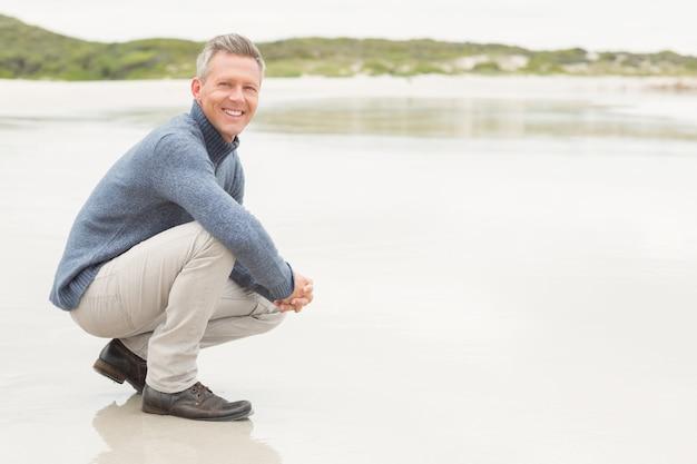男は海岸に腰を下ろした Premium写真