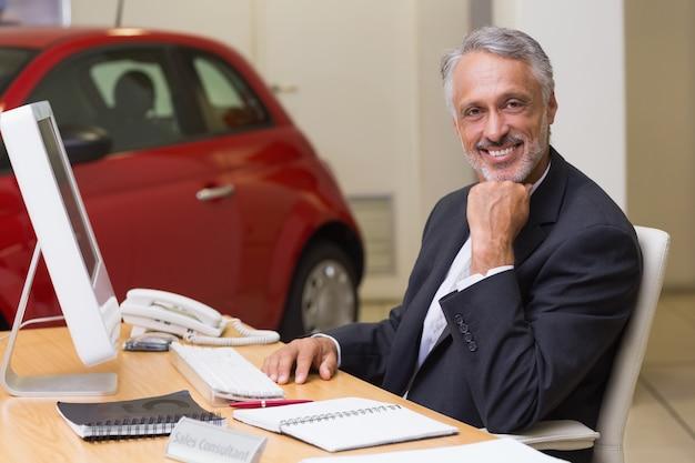 彼の机で働く明るい実業家 Premium写真