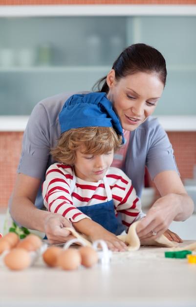 彼の母親と一緒にベーキング小さな男の子 Premium写真