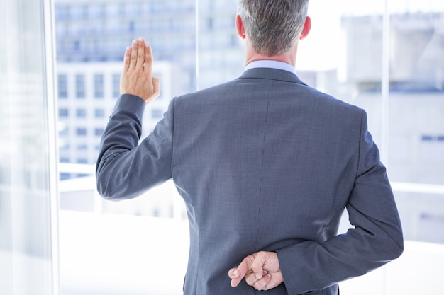 ビジネスマン、指を渡しながら誓いをする Premium写真