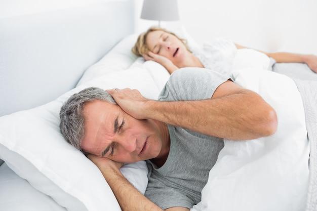 Усталый человек, блокирующий уши от шума жены, храпящей Premium Фотографии