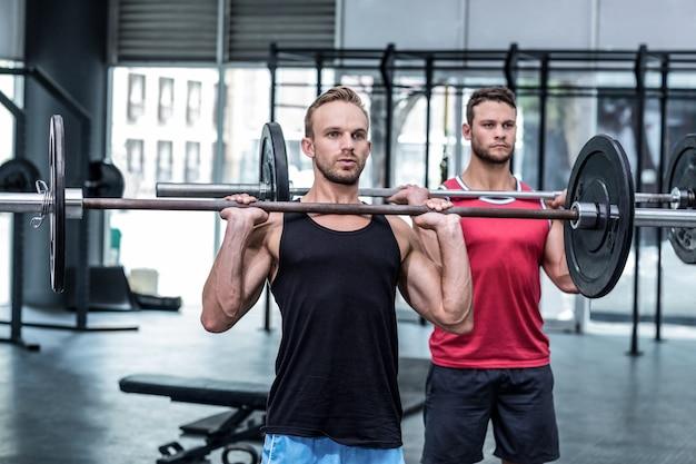 筋肉の男性は、バーベルを持ち上げる Premium写真