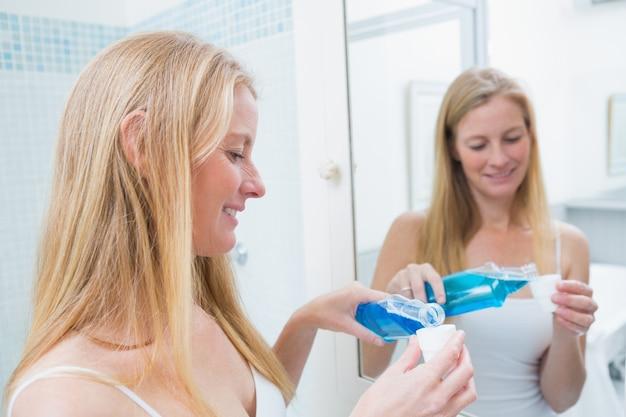 青いうがい薬を注ぐ幸せな女性 Premium写真