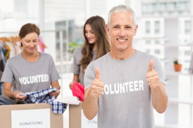 Улыбающийся волонтер, делающий большие пальцы Premium Фотографии