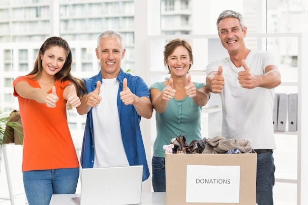 Случайные деловые люди, жертвуя и делая большие пальцы вверх Premium Фотографии