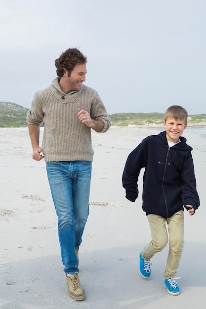 ビーチでジョギングする若い男と息子 Premium写真