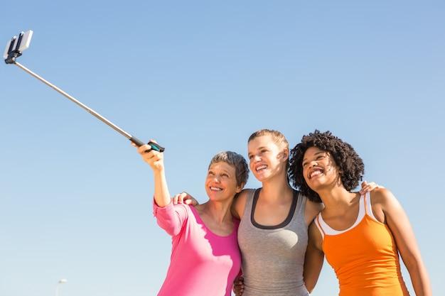 セルフスティックでセルフを撮っている笑顔のスポーティーな女性 Premium写真