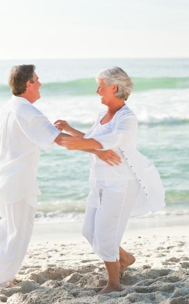 ビーチで踊っている高齢者のカップル Premium写真