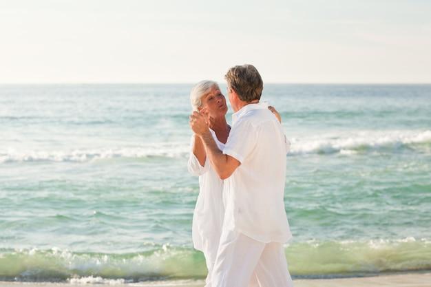 退職したカップルはビーチで踊っている Premium写真