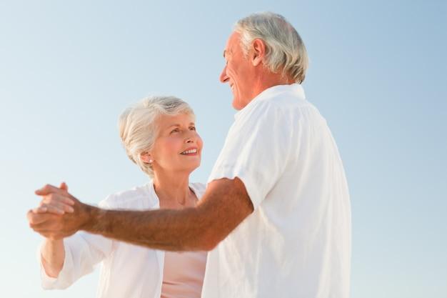 ビーチで踊っているシニアカップル Premium写真
