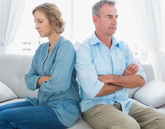 中年のカップルは、戦いの後に話していないソファに座って Premium写真
