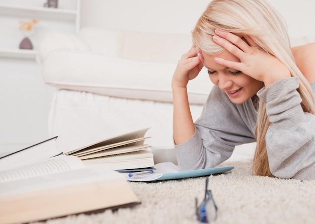Привлекательная белокурая женщина, лежа на ковер сердиться на свой компьютер Premium Фотографии