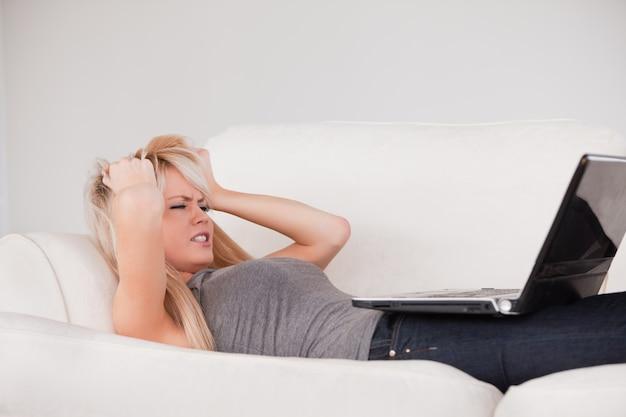 Привлекательная белокурая женщина расстроена своим компьютером, лежащим на диване Premium Фотографии