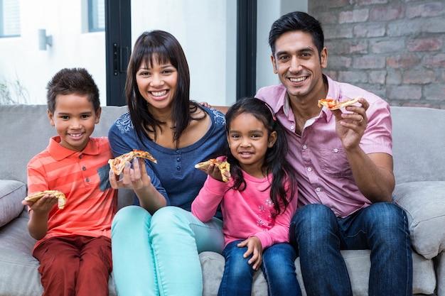 幸せな家族、ピザを食べる、ソファ Premium写真