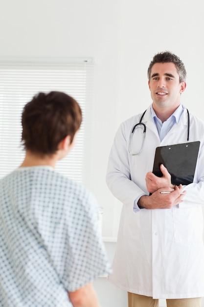 Доктор разговаривает с милой женщиной в больничном платье Premium Фотографии