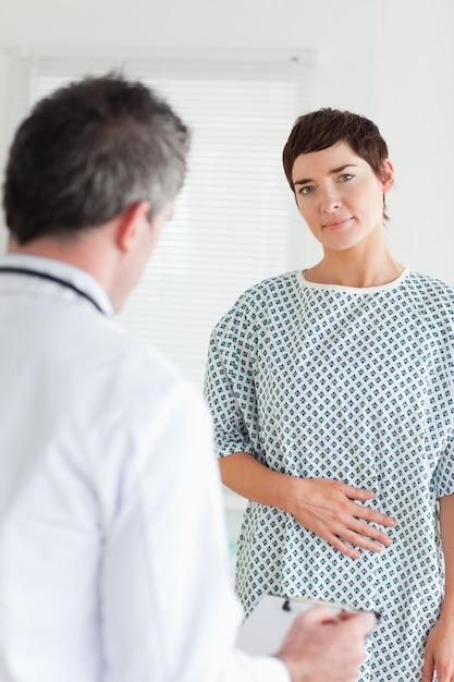 Очаровательная женщина в больничном платье говорить с врачом Premium Фотографии