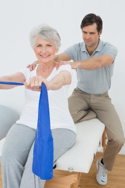 Мужской терапевт, помогая старшей женщине с упражнениями Premium Фотографии