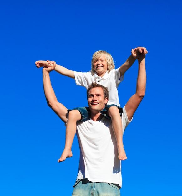 Ребенок сидит на плечах отца Premium Фотографии