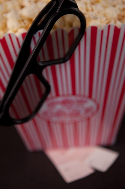 ポップコーンの箱の端に垂れた眼鏡 Premium写真