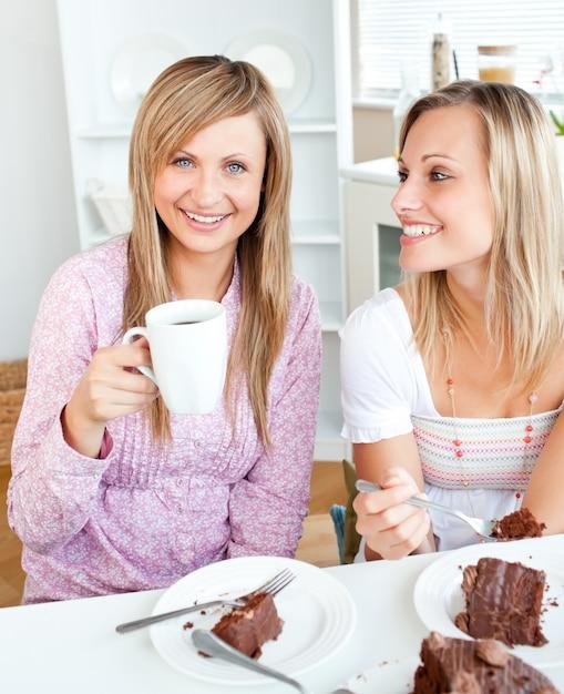 チョコレートケーキを食べて、キッチンで飲む、楽しい女性の友達 Premium写真