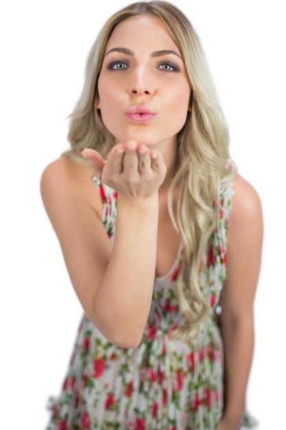 Соблазнительная блондинка в цветущем платье, отправляющая поцелуй Premium Фотографии
