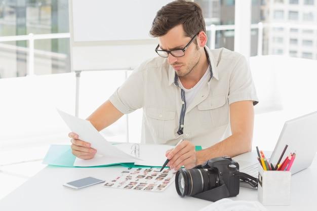 Концентрат мужской художник, сидя на столе с фотографиями Premium Фотографии