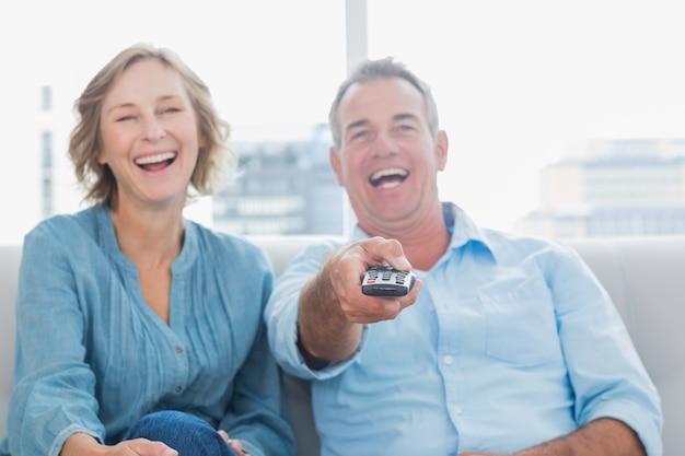 テレビを見てソファに座って中年のカップルを笑う Premium写真