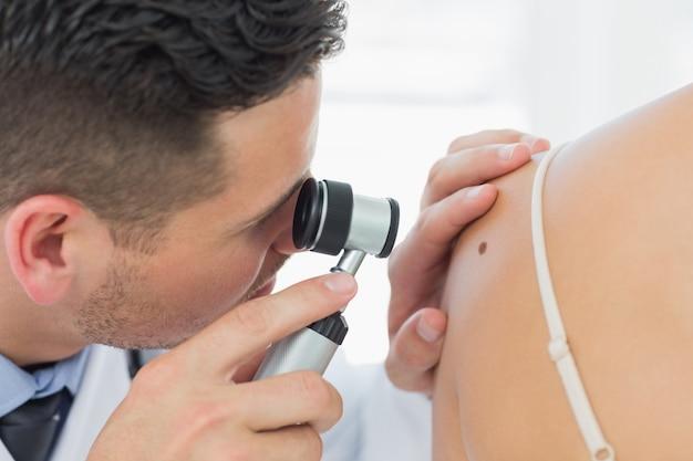 女性の皮膚科学者のモルを確認する Premium写真
