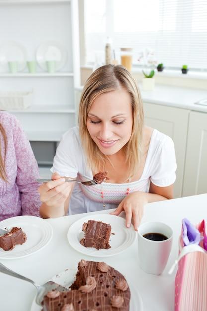 キッチンに座っているチョコレートケーキを食べている美しい女性 Premium写真