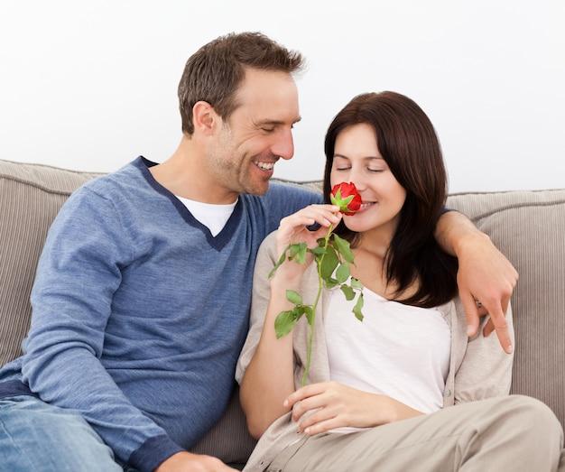 彼のガールフレンドを見てラブリーな男は、赤いバラをにおい Premium写真