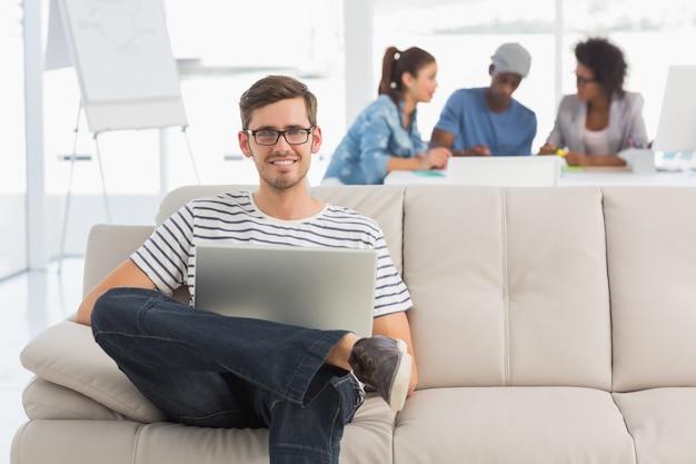 Человек, используя ноутбук с коллегами в фоновом режиме в творческом офисе Premium Фотографии