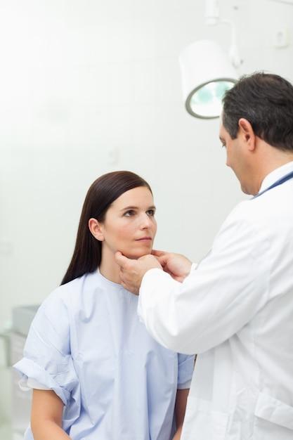 医者が患者の首に触れる Premium写真