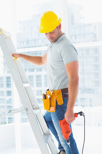 ドリルマシン登山梯子を持つ手動作業員 Premium写真
