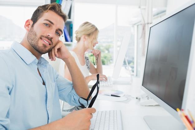 Улыбаясь случайных молодых пара, работающих на компьютере Premium Фотографии