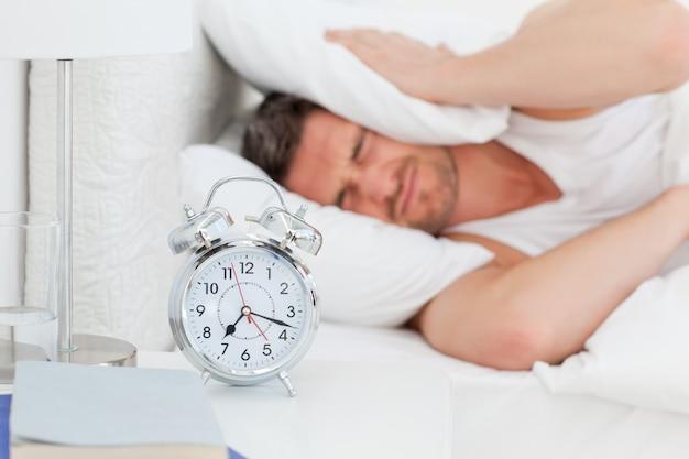 目覚める前に彼のベッドの中で苛立つ男 Premium写真