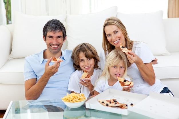Улыбается семья есть пицца, сидя на полу Premium Фотографии