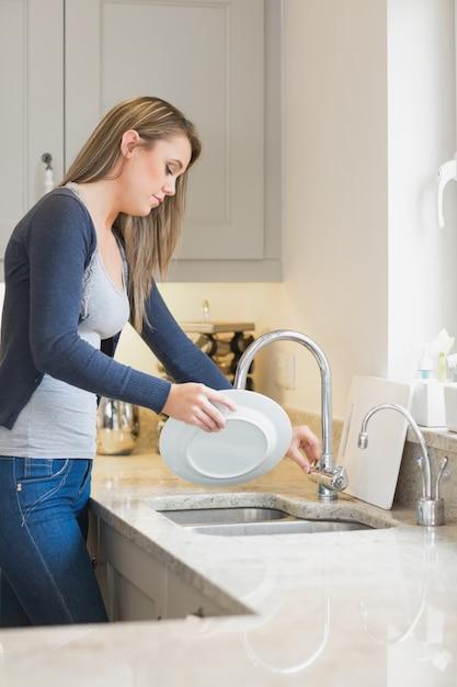 キッチンで洗濯をする女性 Premium写真