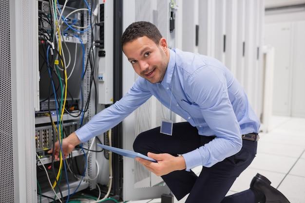 Улыбающийся техник с планшетным пк, подключающим кабели к серверу в дата-центре Premium Фотографии