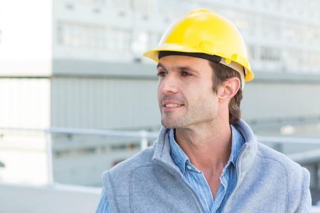 黄色のハード帽子を身に着けている思慮深い Premium写真