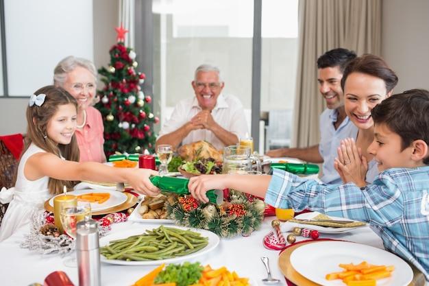 家の中のクリスマスディナーのためのダイニングテーブルで陽気な家族 Premium写真