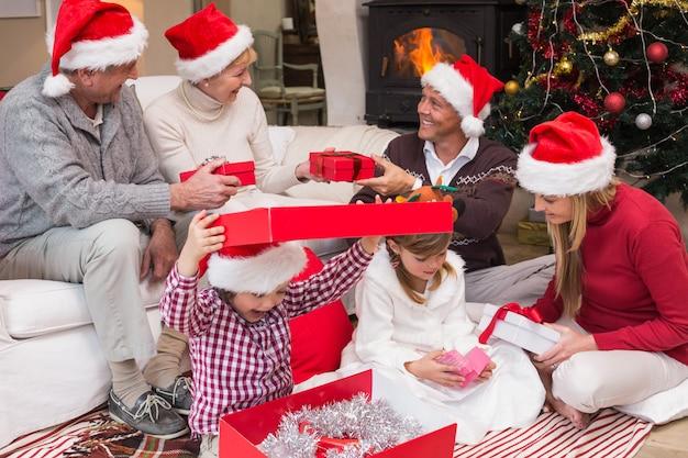 リビングルームで一緒に家庭でクリスマスプレゼントを開く幸せな家族 Premium写真