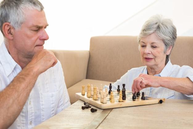 チェスをする床に座っているシニアカップル Premium写真