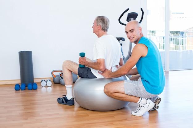 Старик с обратно массаж на осуществление мяч Premium Фотографии