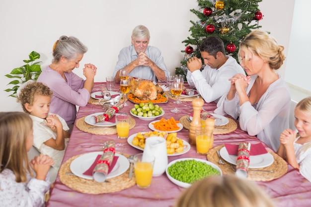 家族はクリスマスディナー前に猶予を言います Premium写真