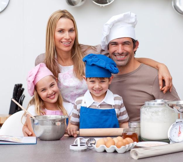キッチンで焼く子供たちを助ける笑顔の親 Premium写真