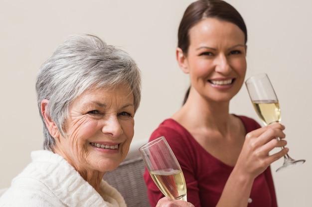 シャンパンのガラスを持っている笑顔の女性 Premium写真