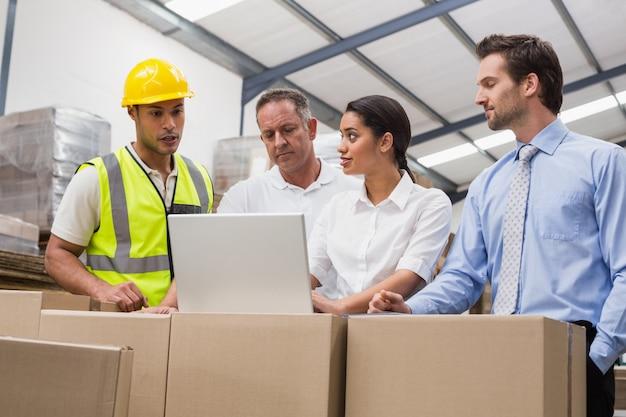 倉庫管理者とノートパソコンを見ている労働者 Premium写真