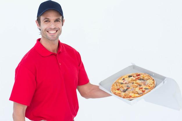 新鮮なピザを持っている幸せな配達人 Premium写真